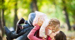 Mujer jugando en un parque con su hijo.